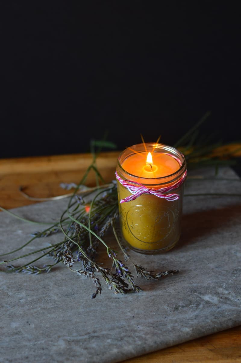 A lit beeswax candle in a mason jar sitting on a rock surrounded by sprigs of lavender.