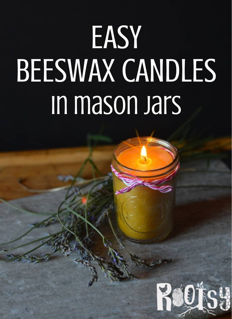 A lit beeswax candle in a mason jar sitting on a rock surrounded by sprigs of lavender with text overlay