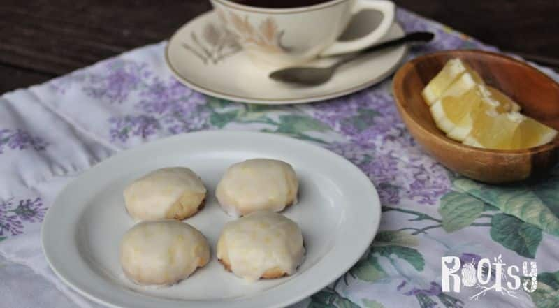 Lemon shortbread cookies on a plat with a cup of tea and lemon wedges beside it.