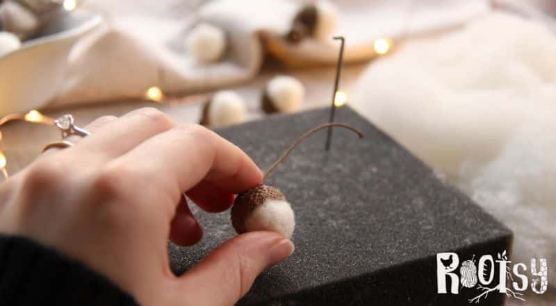 Fingers squeezing felted wool ball into acorn cap.