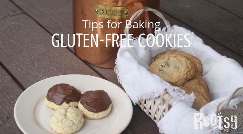 Gluten free cookies on a plate and in a basket in front of a copper cookie jar.