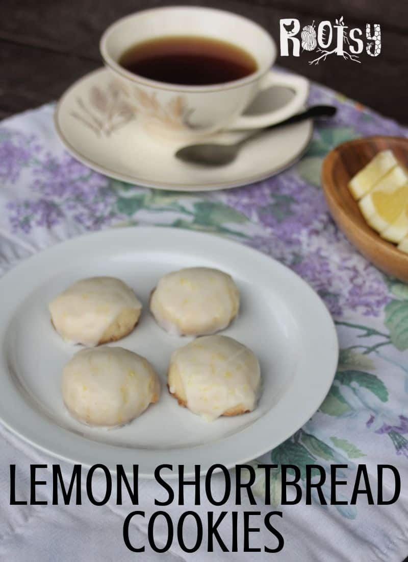 Lemon shortbread cookies on a plate with a cup of tea and lemon wedges beside it.