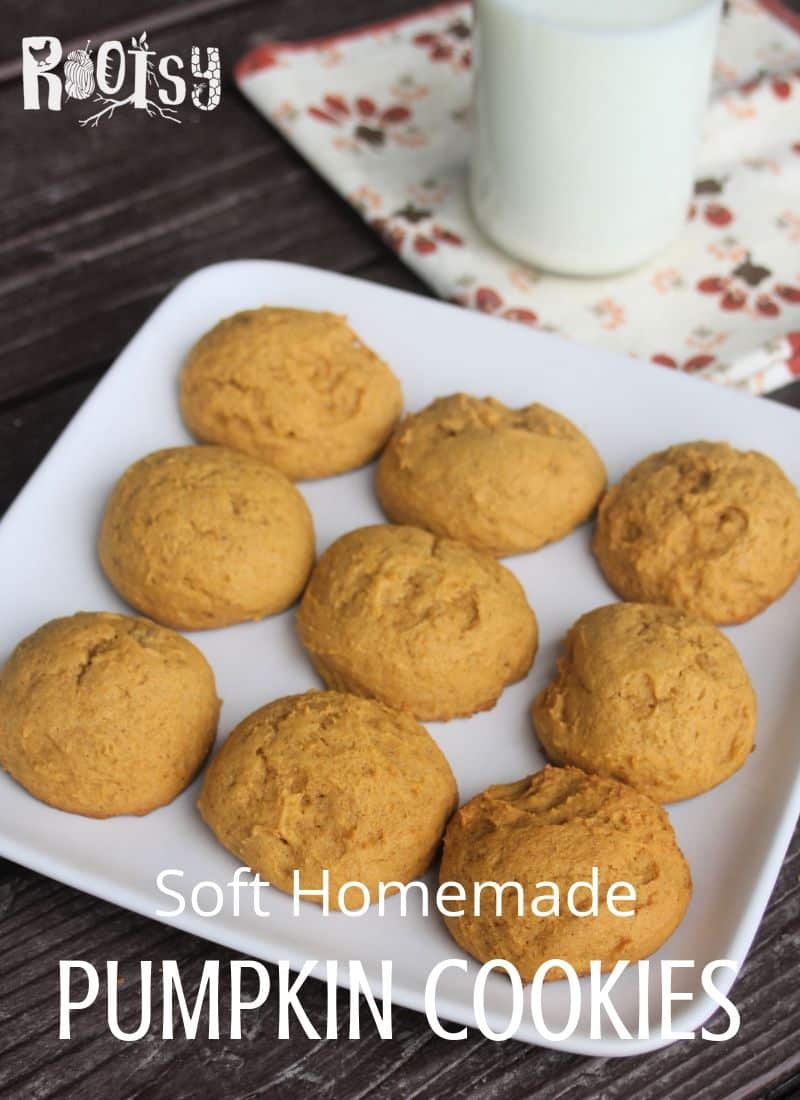 Soft pumpkin cookies on a plate with a napkin and glass of milk.