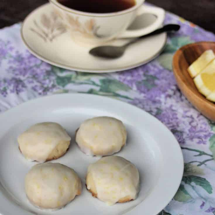 Lemon shortbread cookies on a plate with a cup of tea and lemon wedges on a placemat.
