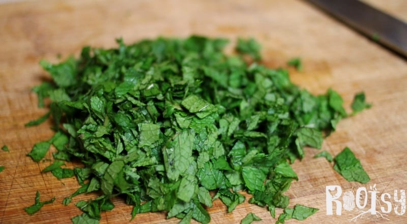 Chopped mint for herb salt. Herbs are easy to grow and produce quite a bit, however, they don't grow year round. Herb salt is a wonderful way to preserve your herb harvest. Learn how to make endless herbal salt combinations today | Rootsy.org