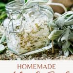 An open square shaped jar full of salt and dried herbs, surrounded by fresh herbs with a text block reading: homemade herb salt.