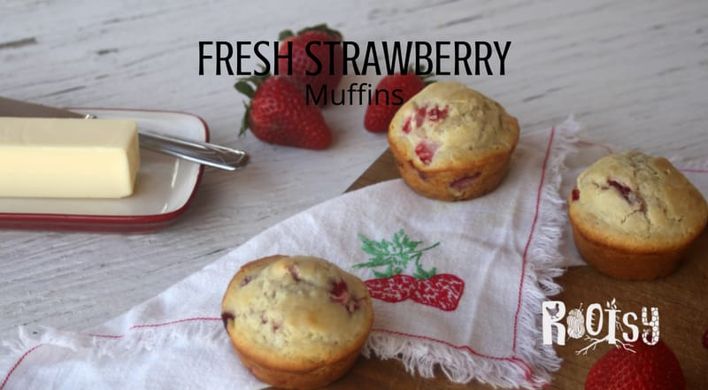 Fresh strawberry muffins on a table with strawberries. Make the most of juicy berries by whipping up these quick and easy fresh strawberry muffins for breakfast and snack time.