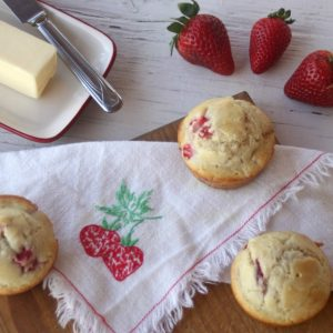 Fresh strawberry muffins on a table with fresh berries and butter.