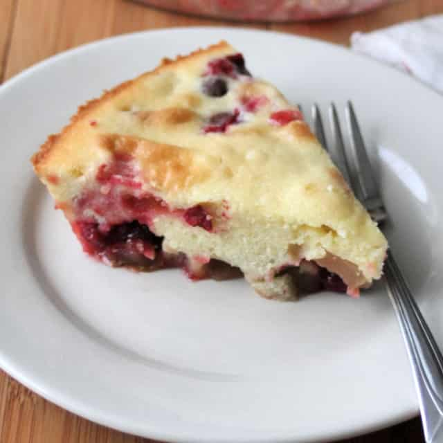 A slice of cranberry pear spoon cake on a plate with a fork.
