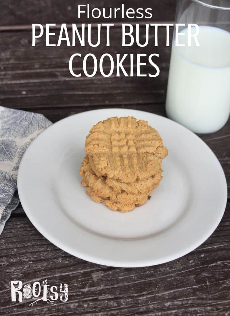 Flourless Peanut Butter Cookies stacked on a plate with a glass of milk.