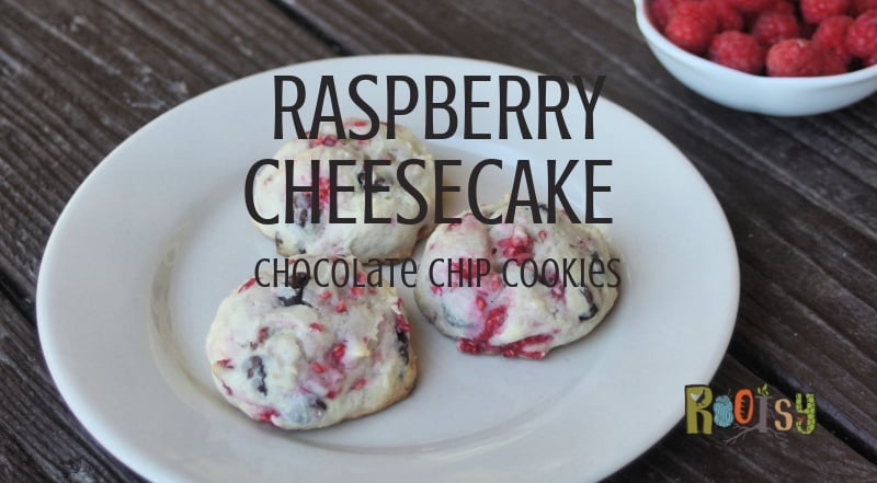 Raspberry cheesecake cookies on a plate in front of a bowl of fresh raspberries.