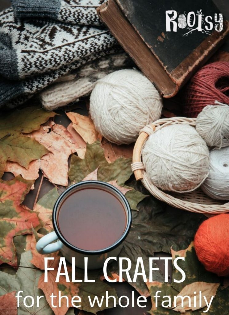 Balls of yarn sitting on top of fall leaves with gloves and old book includes text overlay