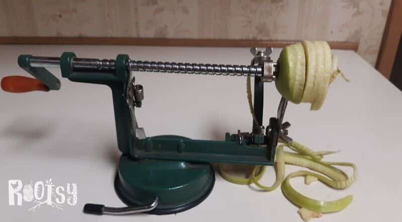 An apple being peeled and cored on a rotary peeling machine.