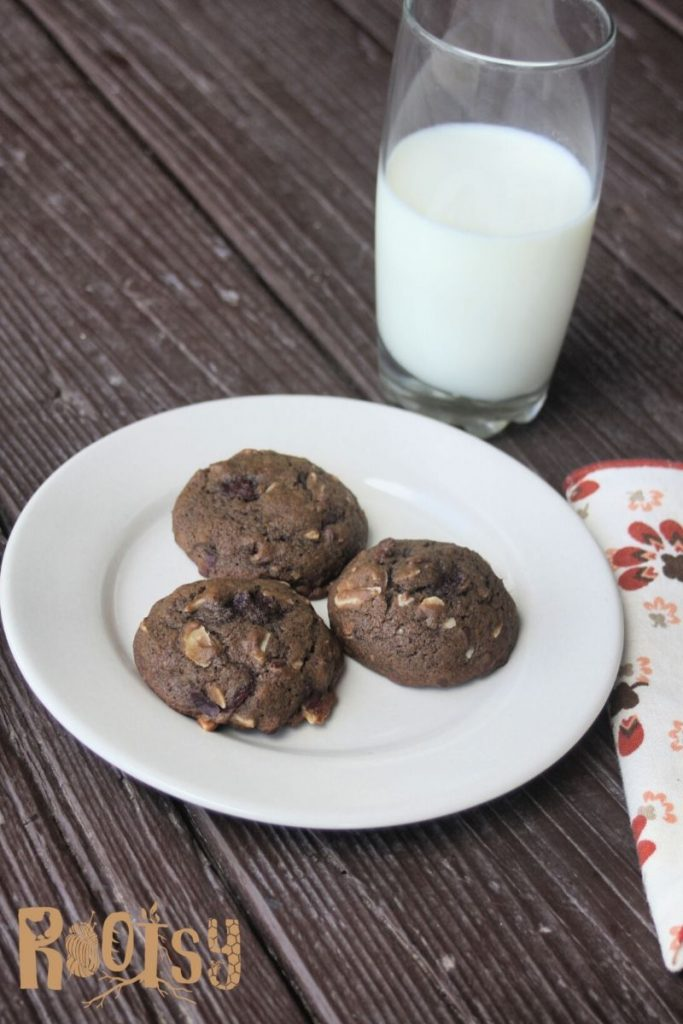 Chocolate cranberry cookies on a plate with a glass of milk and a napkin.