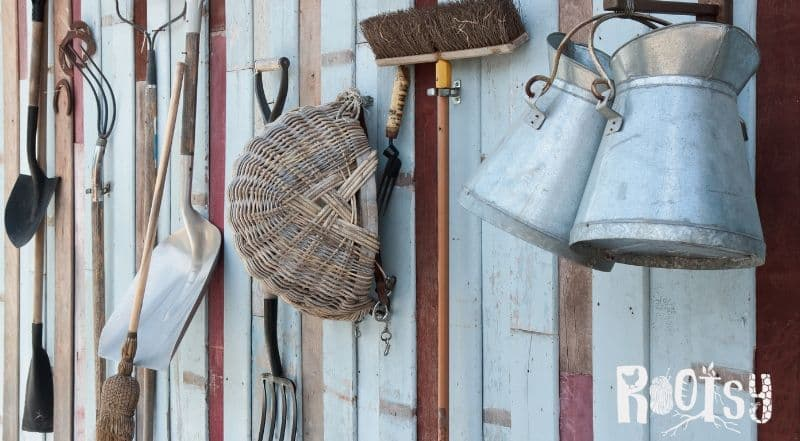 image of garden tools hanging on shed wall for winter