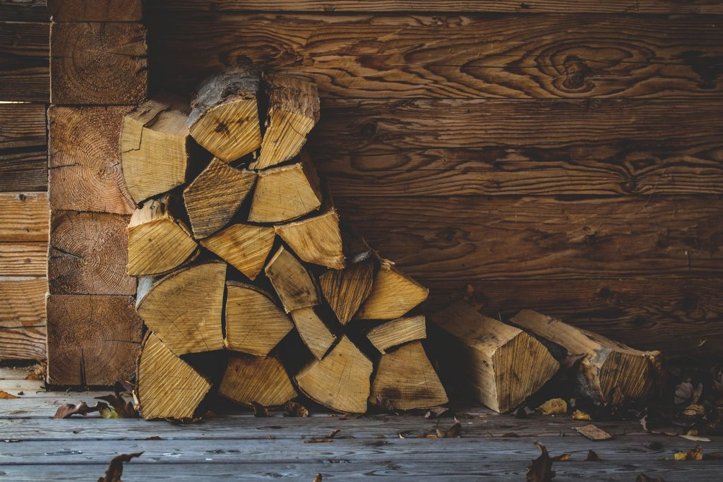 image of firewood stacked against a wood wall