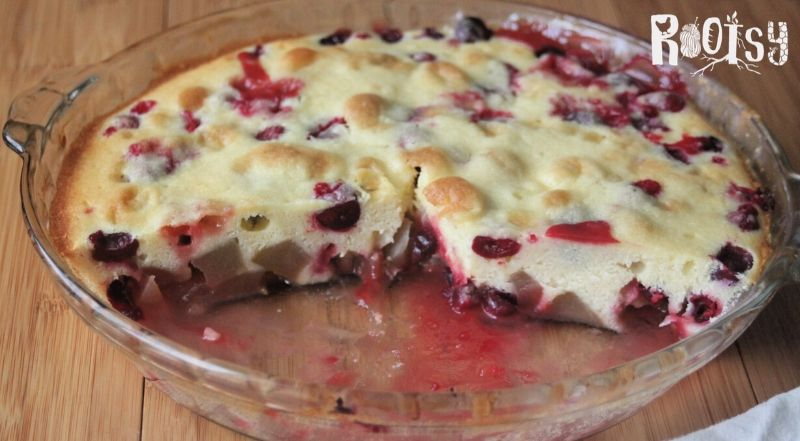 Cranberry pear spoon cake in a glass pie plate with pieces missing.