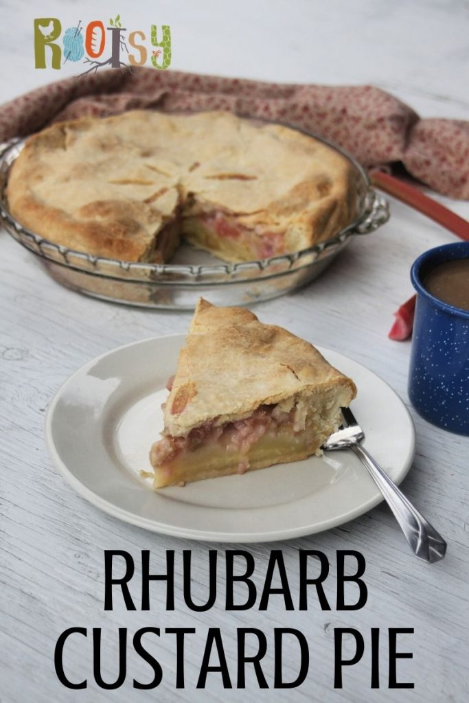 A slice of rhubarb custard pie on a white plate with a fork sitting in front of a whole pie and blue tin cup of coffee.