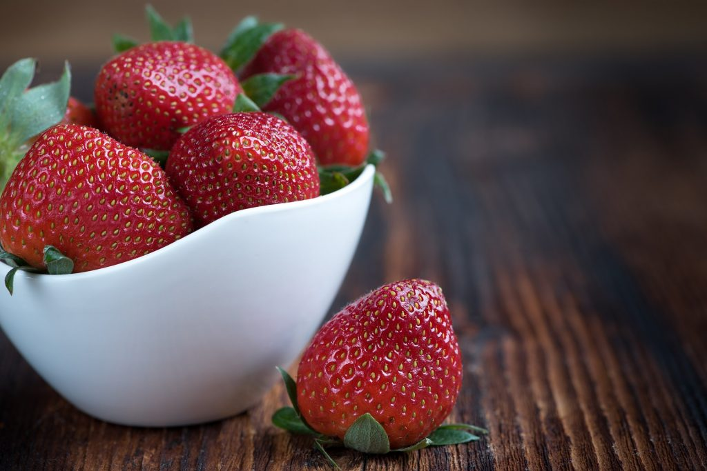 white bowl of fresh strawberries on wooden table.