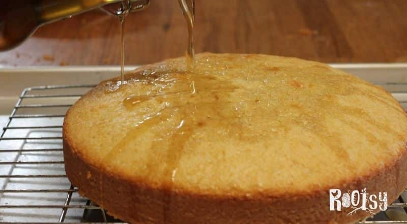 vanilla simple syrup poured on cake