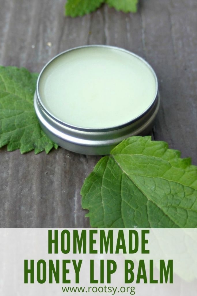 A round metal container full of lip bam surrounded by fresh herb leaves with text overlay stating: homemade honey lip balm.