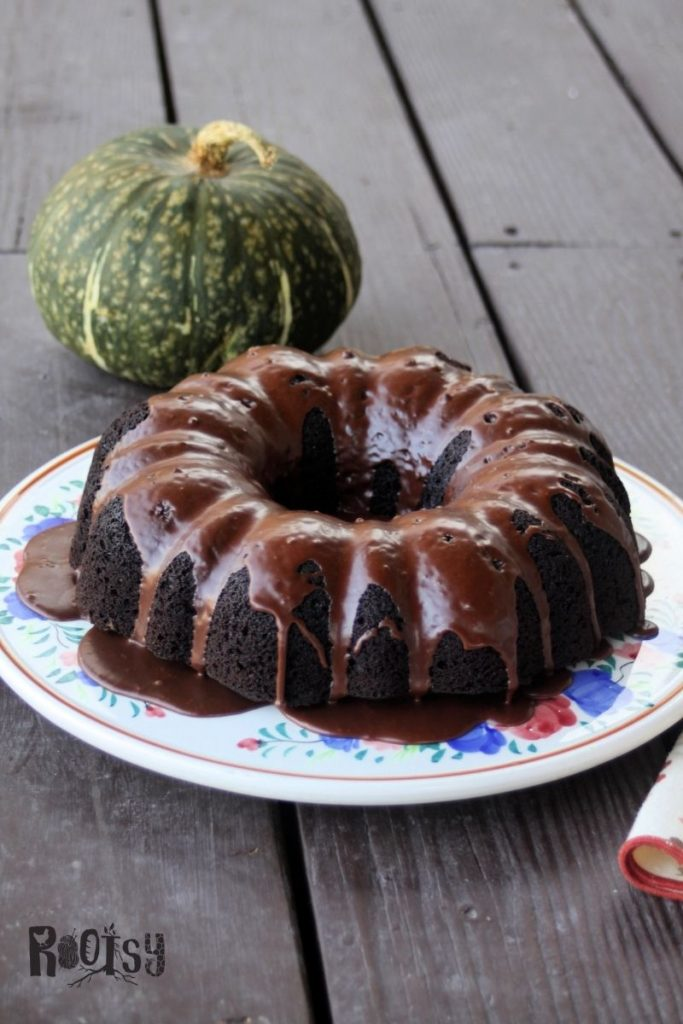 A glazed chocolate pumpkin cake on a floral cake plate with green pumpkin sitting behind it.