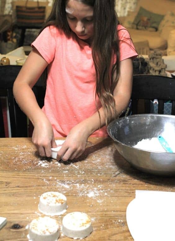 child making bath bombs by pressing the bath bomb recipe into a mold