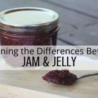 A jar of jam sitting on a wooden cutting board with a spoon full of jam sitting next to it, a text overlay stating: explaining the difference between jam & jelly.