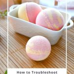 A bath bomb on a bamboo mat in front of a white container of more bath bombs with text overlay reading: how to troubleshoot bath bomb mistakes.