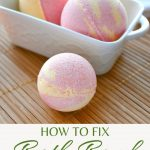 A bath bomb on a bamboo mat in front of a white container of more bath bombs with text overlay reading: how to fix bath bomb mistakes.