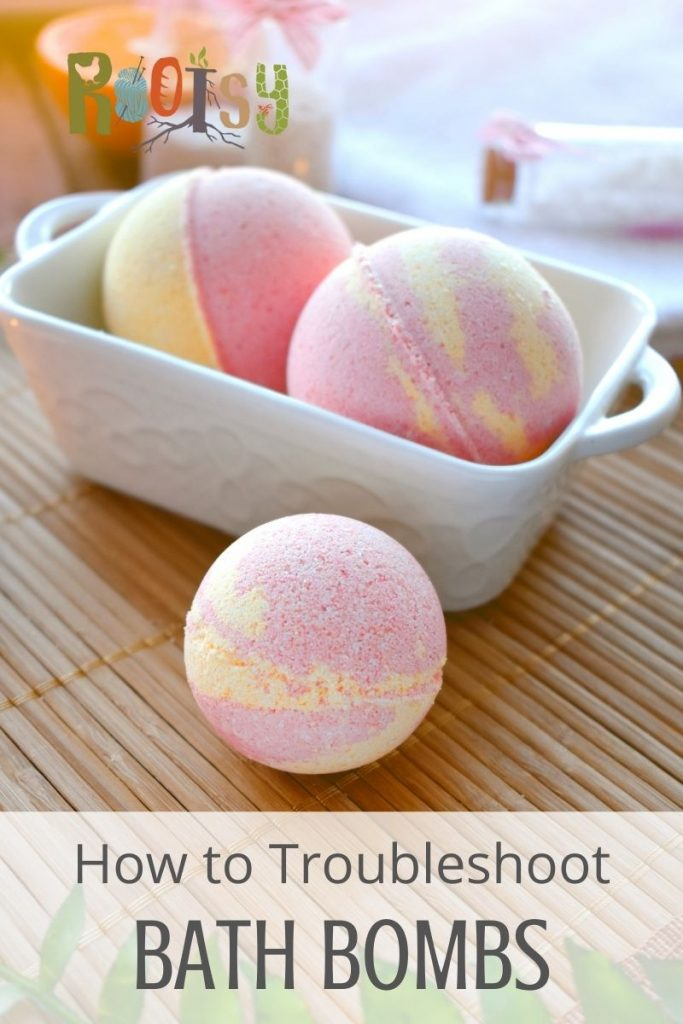 A bath bomb sitting on a bamboo mat in front of a white container with more bath bombs inside and a text overlay stating: how to troubleshoot bath bombs.